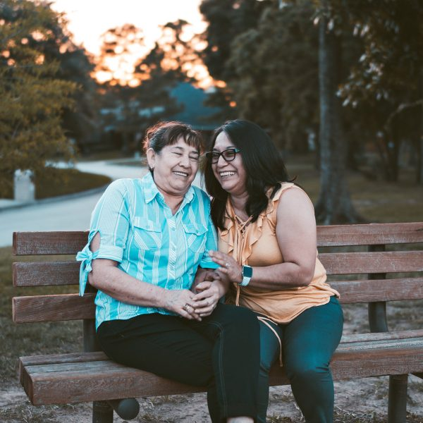 Two senior women laughing on a park bench